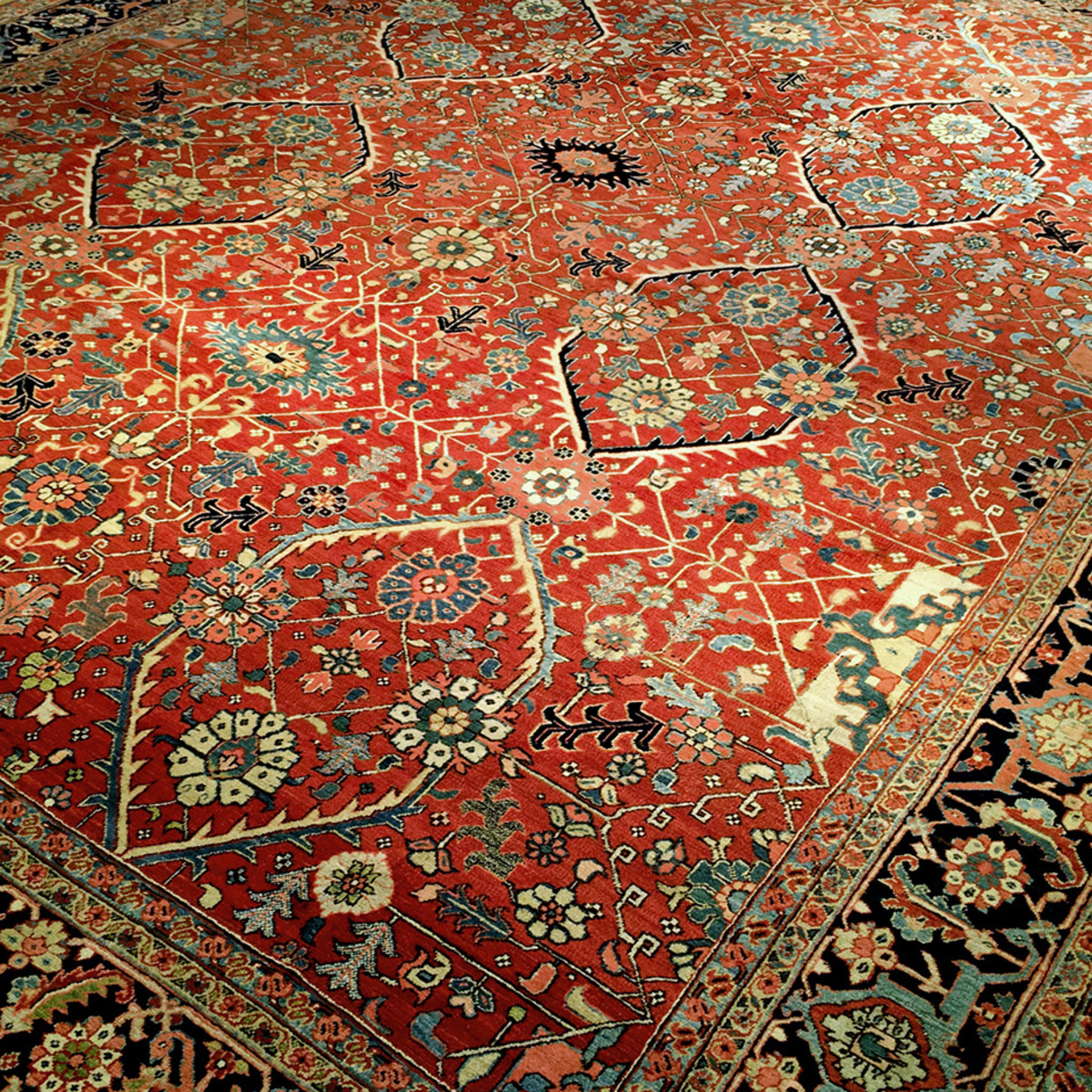 Antique Persian Heriz Serapi carpet with a lattice design on a brick red field that is framed by a navy border
