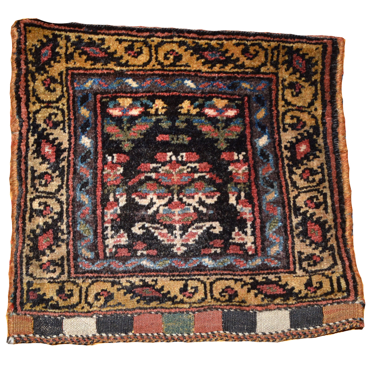 Antique northwest Persian Kurdish bag face with a grouping of flowers on a dark brown field.