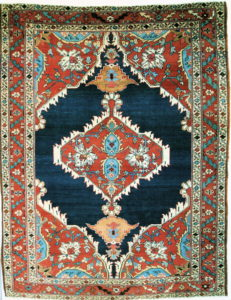 Antique Persian Bakshaish rug with a terra cotta color medallion on a navy blue open field