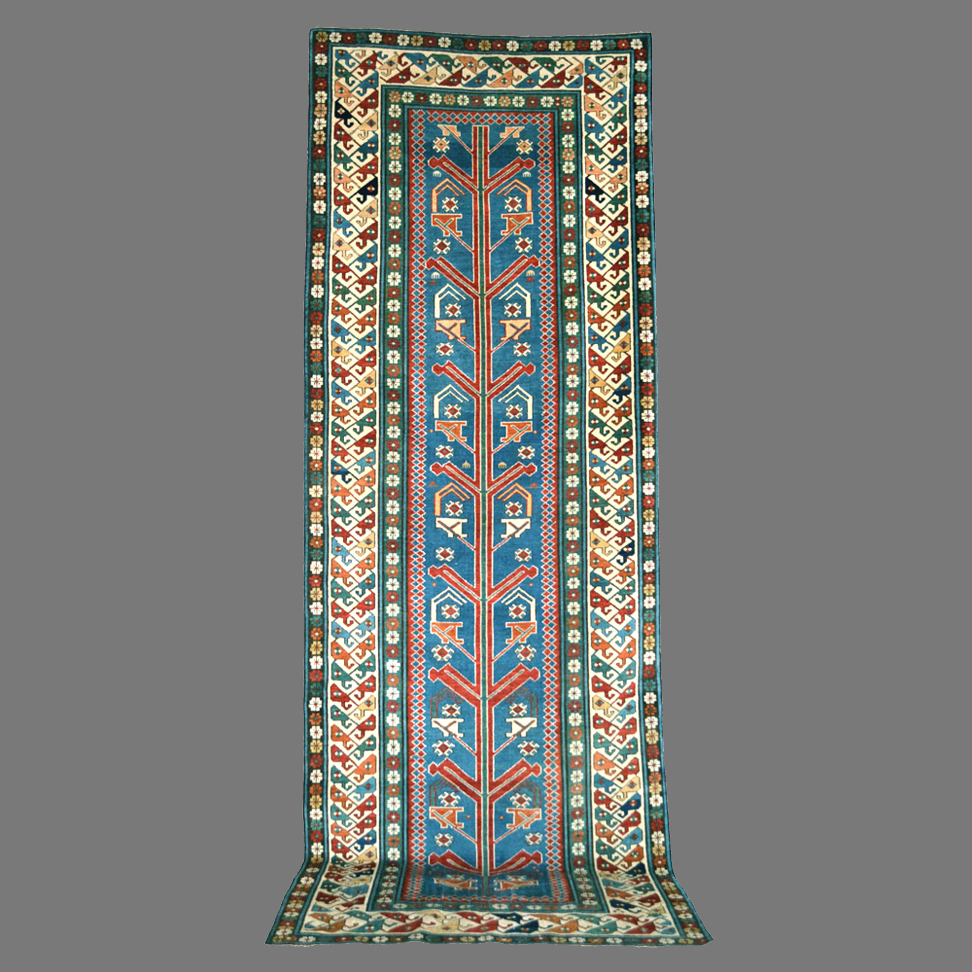 3.2 x 8.9 Antique Caucasian Shirvan long rug with stylized flowers or shrubs on a light blue field, circa 1870